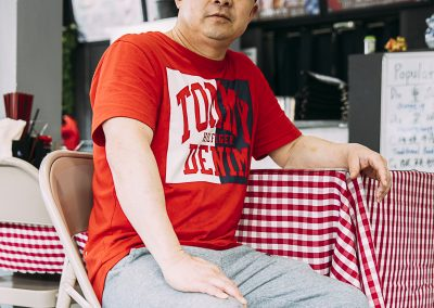 Chef Jimmy Huang sitting at one of the dining tables